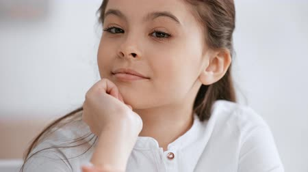 front view of cute preteen child smiling at camera, propping face with hand and looking around