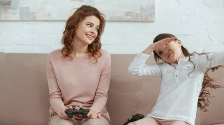excited kid playing video game with mother, enjoying victory and smiling while mother stroking her head
