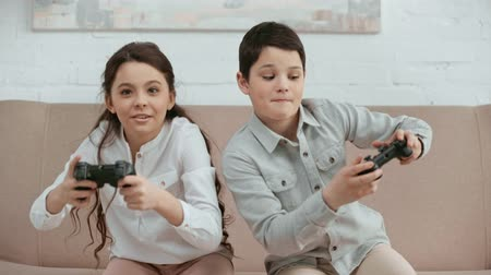 boyhood : front view of two laughing kids sitting on sofa, holding joysticks and pushing each other while playing video game
