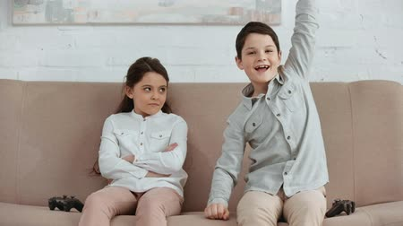 szemléltető : two excited kids holding joystick and playing video game while sitting on sofa in living room