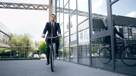 handsome businessman in formal wear riding bike near building