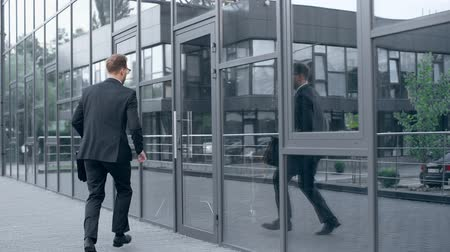 businessman with briefcase running late, opening door, entering building and then walking out Stok Video