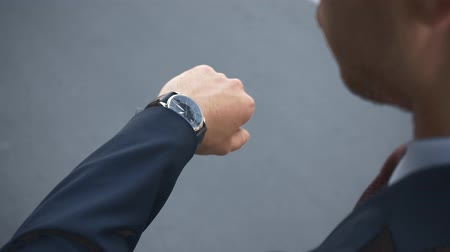 back view of businessman raising hand and looking at watch on gray Stok Video