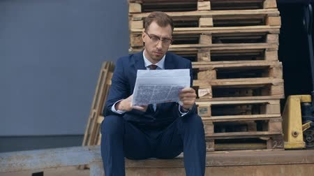 газета : businessman reading newspaper while sitting near wooden pallets and drinking coffee to go