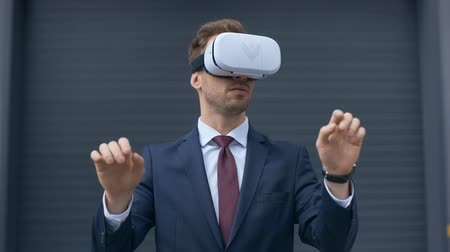 desgaste formal : businessman in virtual reality headset gesturing near gray wall