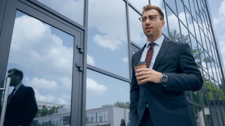 confident businessman drinking coffee to go and walking near building