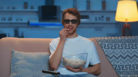 controlador : front view of smiling man in 3d glasses sitting on sofa and eating popcorn while watching tv in living room Stock Footage