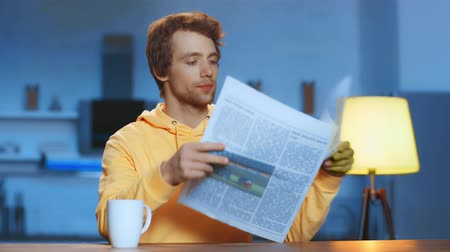 газета : focused man sitting at table in kitchen, drinking tea, reading newspaper and turning pages