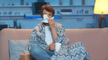 front view of ill young man sitting on sofa under blanket, coughing, using napkin while blowing his nose, drinking tea and watching tv in living room Stok Video