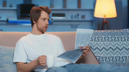 газета : focused young man in white t-shirt drinking tea and reading newspaper while sitting on sofa in living room Стоковые видеозаписи