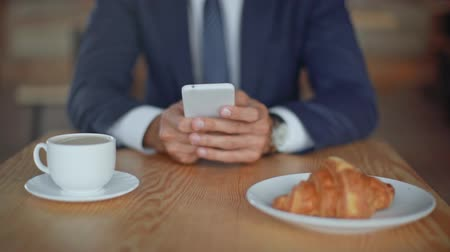 wooden type : cropped view of businessman sitting at table near plate with croissant and cup of coffee and using smartphone