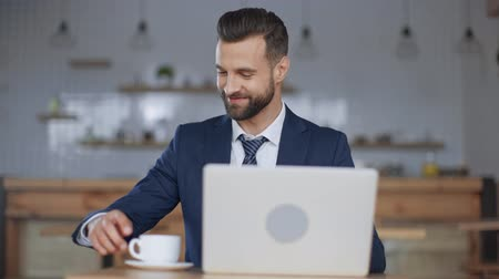 garçonete : cropped view of waitress bringing cup of coffee to smiling, handsome businessman sitting at table near laptop