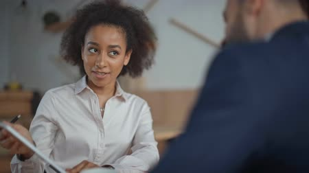 selective focus of positive african american businesswoman smiling and gesturing while talking to businessman in cafe