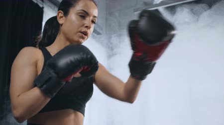 beautiful focused sportswoman exercising with punching bag in gym