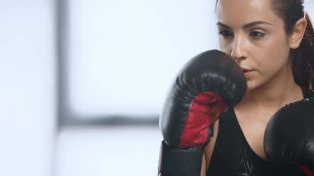 punching bag : beautiful focused sportswoman training with punching bag in sports center