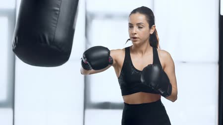 beautiful focused sportswoman training with punching bag in gym