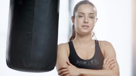 esportivo : beautiful sportswoman stretching, smiling and looking at camera near punching bag in sports center Stock Footage