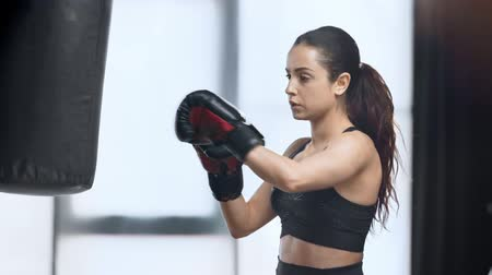 punching bag : beautiful focused sportswoman exercising with punching bag in gym