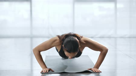 esportivo : young sportswoman doing push ups on fitness mat in sports center Vídeos