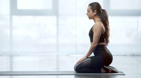 beautiful young sportswoman stretching on fitness mat in sports center