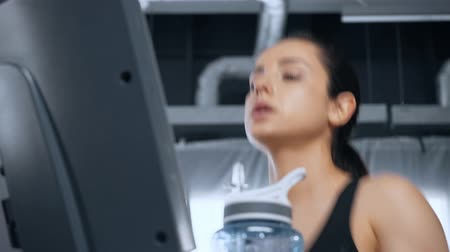 low angle view of beautiful young sportswoman running on treadmill in gym