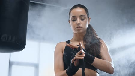 beautiful sportswoman bandaging hands near punching bag in sports center with smoke