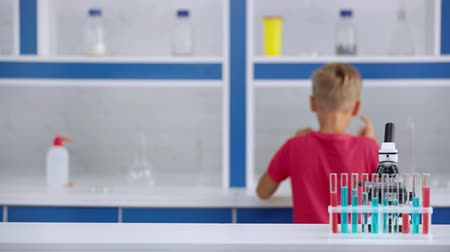 focus pull : rack focus of cute boy in laboratory