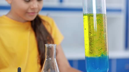 elementary age : selective focus of colorful test tube near girl