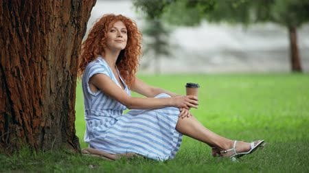eldobható : happy young woman drinking coffee to go in park Stock mozgókép