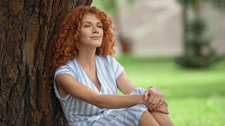 redhair : happy redhead girl sitting near tree trunk