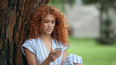 redhair : surprised redhead girl using smartphone in park