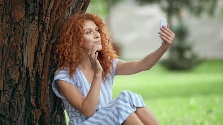 redhair : cheerful redhead girl touching face while taking selfie Stock Footage