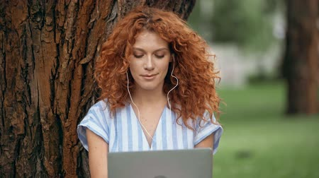 redhair : curly woman using laptop and listening music in park