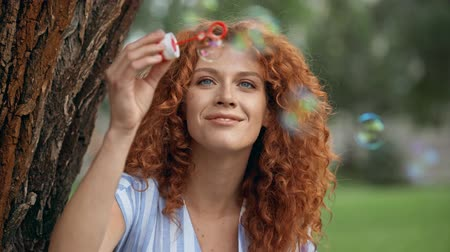 redhair : cheerful redhead woman blowing soap bubbles Stock Footage