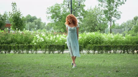 redhair : cheerful redhead girl gesturing and jumping in park