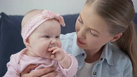 headband : happy mother kissing cheek of baby daughter