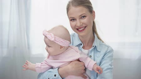 saç bantı : cheerful woman holding in arms baby daughter Stok Video