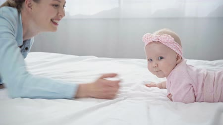 headband : happy mother playing with infant daughter on bed