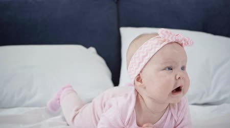 headband : selective focus of adorable infant rolling over on bed