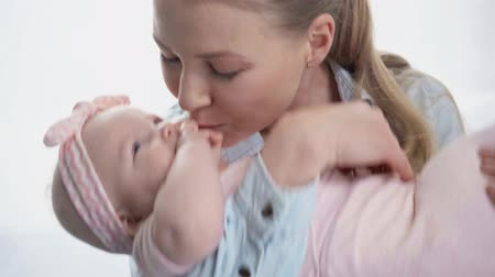 headband : happy mother kissing cute baby at home