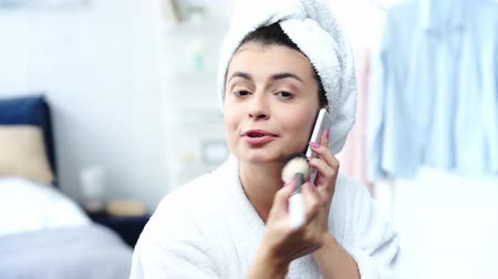 装飾品 : happy woman in bathrobe applying face powder and talking on smartphone