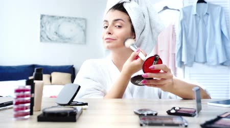 woman applying face power with cosmetic brush near table with decorative cosmetics