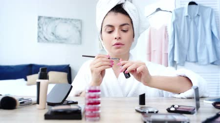 woman applying lipstick with cosmetic brush near table with decorative cosmetics Filmati Stock