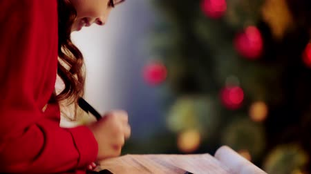 elementary age : cheerful kid writing letter to santa