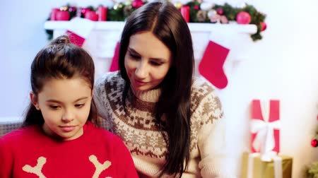 kousen : mother and daughter reading book on christmas Stockvideo
