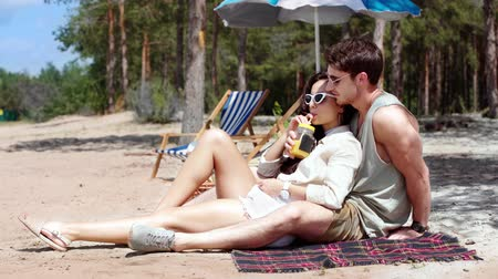 juice jar : cheerful young couple resting on beach and drinking juice from jar with straw