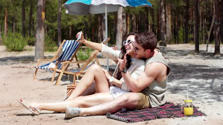 juice jar : happy young couple talking, smiling and taking selfie on smartphone while resting on beach