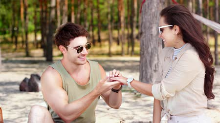 proposta : happy young man making wedding proposal to attractive girlfriend, putting ring on finger and kissing her hand