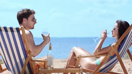 kırmızı şarap : young couple sitting in chaise lounges on beach and clinking glasses with red wine