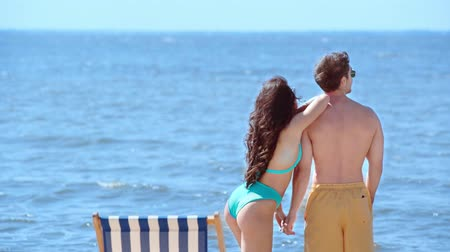 gömleksiz : beautiful young woman in swimsuit hugging boyfriend pointing with finger at skyline